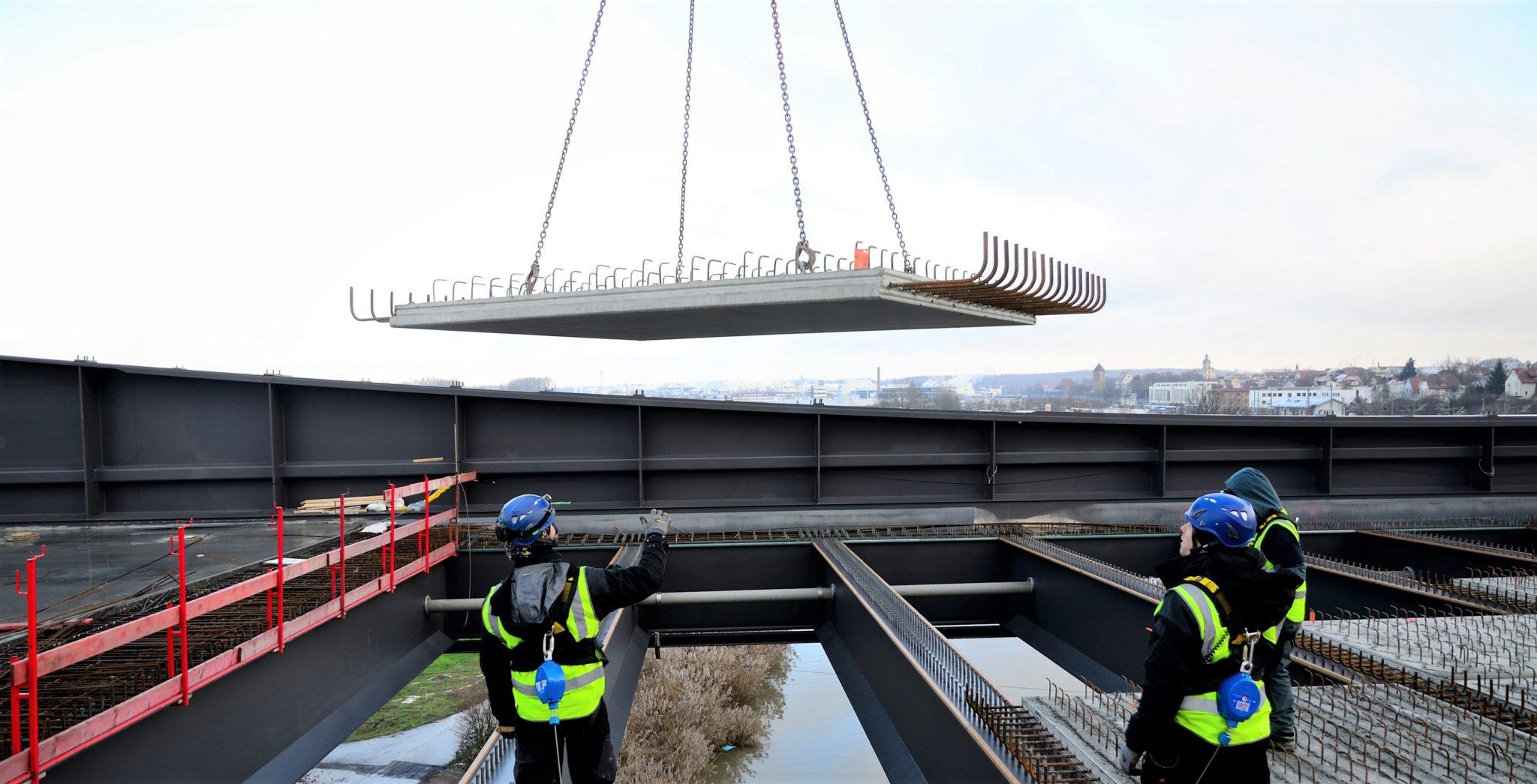 Die Höhenarbeiter sind gesichert. Sie arbeiten auf den Stahlträgern über dem Neckar, nehmen die Betonplatten vom Kran in Empfang und platzieren sie auf den Trägern. Quelle: Heilbronner Stimme